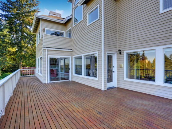 Two Story House With Wooden Walkout Deck Overlooking Backyard